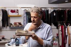 Mens die schoenen kiezen tijdens schoeisel die bij schoenwinkel winkelen royalty-vrije stock foto