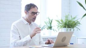 Mens die in schok aan laptop werken stock video