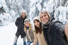 Mens die Selfie-de Glimlachsneeuw Forest Young People Group Outdoor nemen van Fotovrienden Royalty-vrije Stock Foto