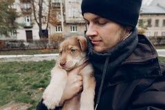 Mens die selfie met aanbiddelijk bruin puppy met verbazende blauwe ey nemen stock foto's