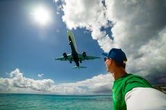 Mens die selfie met vliegtuig nemen die over op beroemd Maho-strand vliegen royalty-vrije stock afbeelding