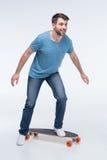 Mens die skateboard op wit proberen te berijden stock afbeeldingen
