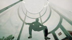 Mens die skydiver in een binnenarena skydiving Het vliegen in een windtunnel stock footage