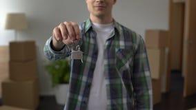 Mens die sleutel van flat tonen, het betaalbare lenen, investering in onroerende goederen stock footage
