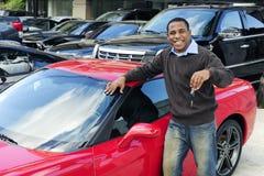 Mens die sleutel van nieuwe rode sportwagen toont Stock Foto