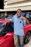 Mens die sleutel van nieuwe rode sportwagen toont Royalty-vrije Stock Afbeelding