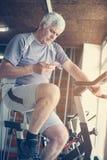 Mens die slimme telefoon in de gymnastiek met behulp van Mens het typen berichten  Stock Foto's