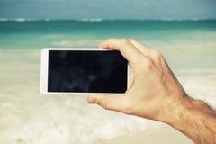Mens die slimme telefoon voor het nemen van foto op een strand met behulp van Royalty-vrije Stock Foto's