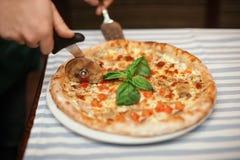 Mens die smakelijke oven gebakken pizza op lijst snijdt royalty-vrije stock fotografie