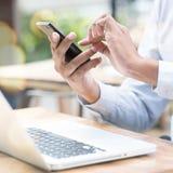 Mens die smartphone en laptop computer met behulp van openlucht Stock Foto