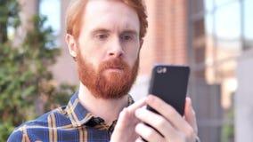 Mens die smartphone gebruiken terwijl openlucht zitten stock video