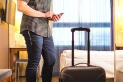 Mens die smartphone in hotelruimte gebruiken met bagage en koffer stock afbeeldingen