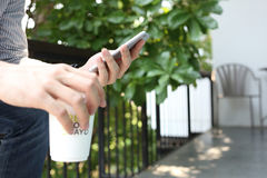 Mens die smartphone met holdings coffe document kop met groen weiland gebruiken Stock Afbeeldingen