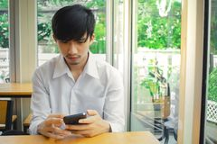 Mens die smartphone naast venster kijken stock fotografie
