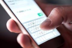 Mens die sms-bericht en sms met smartphone verzenden Kerel die en mobiele telefoon texting met behulp van laat bij nacht in dark royalty-vrije stock afbeelding