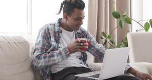 Mens die snack hebben terwijl het letten op de media op laptop tevredenstellen stock video