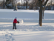 Mens die Sneeuw schept Stock Foto's