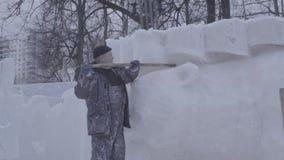 Mens die Sneeuw schept Maak beeldhouwwerk van sneeuw wordt gemaakt die Het sneeuwbeeldhouwwerk, blokkeert Opgestapeld Wachten voo stock video