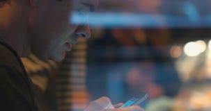 Mens die in sociale media op slimme telefoon babbelen stock footage