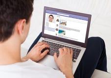 Mens die sociale voorzien van een netwerkplaats op laptop thuis gebruiken Stock Fotografie
