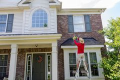 Mens die soffits of eaves van een modern huis wassen royalty-vrije stock foto's