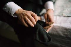 Mens die sokken op zijn voetenclose-up zetten in slaapkamer stock afbeelding