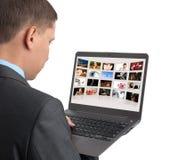 Mens die sommige beelden op laptop kijkt stock foto's