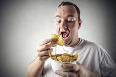 Mens die spaanders eet stock afbeeldingen