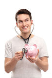 Mens die spaarvarken met stethoscoop onderzoekt Stock Foto's