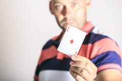 Mens die speelkaart in zijn hand tonen stock foto's