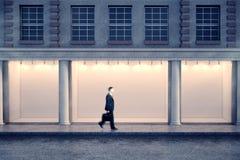 Mens die storefront bij nacht overgaan Stock Fotografie