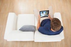 Mens die strandmening thuis bekijken over digitale tablet Stock Foto