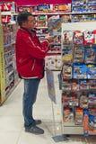 Mens die stuk speelgoed voor kind in opslag kiezen Planken met speelgoed Winkel voor kinderen stock foto's