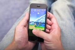 Mens die Super Mario Run-spel app op iPhone spelen royalty-vrije stock fotografie