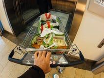 Mens die supermarktlift met volledig boodschappenwagentje ingaan royalty-vrije stock foto's