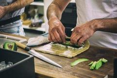 Mens die sushimaaltijd met avocado voorbereiden bij open voedselmarkt in Ljubljana, Slovenië Royalty-vrije Stock Fotografie