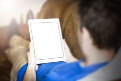 Mens die tablet gebruiken terwijl het liggen op bank Royalty-vrije Stock Foto's
