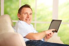 Mens die tablet in huis gebruikt Stock Fotografie
