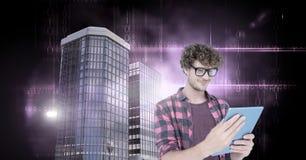 Mens die tablet met Lange gebouwen met donkere binaire codegloed gebruiken Royalty-vrije Stock Afbeelding