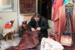 Mens die tapijt in Istanboel maken Stock Foto