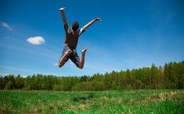 Mens die tegen blauwe hemel springt stock afbeeldingen