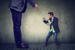 Mens die tegen zijn grote werkgever vechten stock fotografie