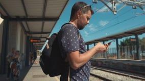 Mens die telefoon op station met behulp van stock videobeelden