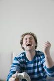 Mens die terwijl de Console van het Holdingsvideospelletje lachen Stock Foto