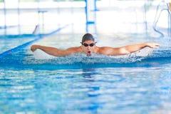 Mens die terwijl het zwemmen van vlinderslag ademt Stock Afbeelding