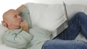 Mens die thuis en op Sofa Doing Business Using Laptop zitten rusten stock fotografie