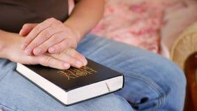 Mens die thuis houdend een Heilige Bijbel bidden stock videobeelden