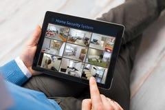 Mens die thuis veiligheidscamera's op tabletcomputer kijken