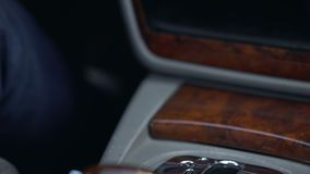 Mens die toestel, automatische transmissie, luxeauto met houten binnenland verplaatsen stock footage