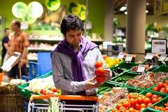 Mens die tomaten in een verse voedselsectie kiest Stock Foto's